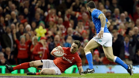 Wales' George North, left, goes over the line to score a try next to Italy's Mattia Bellini, right, during the Six Nations rugby union match between Wales and Italy at the Principality Stadium in Cardiff, Wales, Sunday, March 11, 2018. (AP Photo/Alastair Grant)