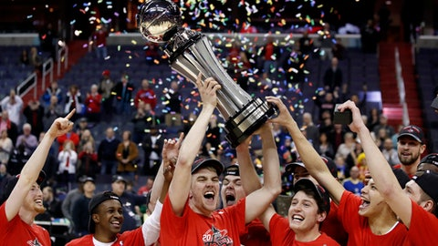 Davidson forward Peyton Aldridge, center, holds the trophy with his teammates after an NCAA college basketball championship game against Rhode Island in the Atlantic 10 Conference tournament, Sunday, March 11, 2018, in Washington. Davidson won 58-57. (AP Photo/Alex Brandon)