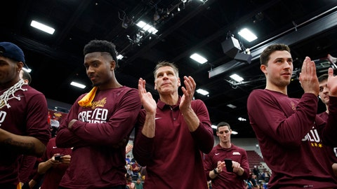 From left, Loyola Ramblers guard Donte Ingram, head coach Porter Moser, and Ramblers guard Ben Richardson stand with other players after the Loyola men's basketball team was selected to play in the NCAA Tournament during a selection show watch party at Gentile Arena Sunday, March 11, 2018 in Chicago. (Armando L. Sanchez/Chicago Tribune via AP)