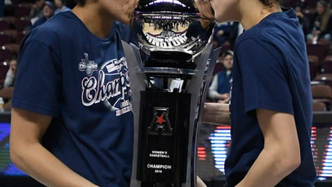FILE - In this March 6, 2018, file photo, Connecticut's Gabby Williams and Kia Nurse, right, kiss the American Athletic Conference championship trophy after an NCAA college basketball game against South Florida in the final of the conference's women's tournament, in Uncasville, Conn. UConn finishes No. 1 in The Associated Press women's basketball poll for the fifth straight year. The Huskies (32-0) enter the NCAA Tournament as the lone unbeaten team and went wire-to-wire as the unanimous top team. They received all 32 votes from the national media panel Monday, March 12, 2018. (AP Photo/Jessica Hill, File)