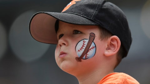 FILE - In this Aug. 6, 2017, file photo, a young baseball fan looks on before the Baltimore Orioles and Detroit Tigers baseball game, in Baltimore. The Orioles have launched a program that will enable kids to attend home games this season free of charge. Fulfilling a childs request to take me out to the ballpark has become a lot cheaper at Camden Yards. Every adult who purchases a regularly-priced upper deck ticket can bring up to two children, age 9 or under. (AP Photo/Gail Burton, File)