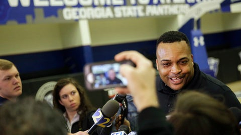 Georgia State head coach Ron Hunter, right, talks to reporters during an NCAA college basketball practice in Atlanta, Monday, March 12, 2018. When Georgia State last appeared in the NCAA Tournament, Hunter was tumbling off his stool after his son hit a memorable shot. The coach is fully healthy this time around and hoping the Panthers can pull off another major surprise. (AP Photo/David Goldman)