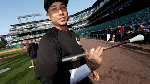 FILE - In this Sept. 29, 2017, file photo, Colorado Rockies right fielder Carlos Gonzalez heads back to the dugout after warming up for a baseball game against the Los Angeles Dodgers in Denver. The Rockies finalized a $5 million, one-year deal to bring back three-time All-Star and popular clubhouse leader Gonzalez. His agreement was announced Monday, March 12, 2018, and includes $3 million in bonuses based on days on the active roster. (AP Photo/David Zalubowski, File)