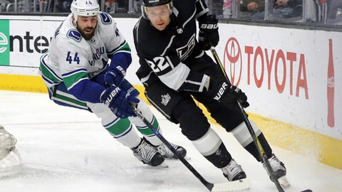 Los Angeles Kings center Trevor Lewis (22) and Vancouver Canucks defenseman Erik Gudbranson (44) chase the puck in the second period of an NHL hockey game in Los Angeles, Monday, March 12, 2018. (AP Photo/Reed Saxon)
