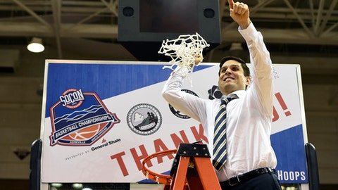 FILE - In this March 5, 2018, file photo, UNC-Greensboro head coach Wes Miller holds the basketball net in the air to celebrate his team's 62-47 win over East Tennessee State in the NCAA college basketball championship game for the Southern Conference, in Asheville, N.C. Miller is the youngest head coach in the NCAA Tournament but he still has plenty of experience. The 35-year-old, seventh-year coach is preparing the Spartans for their first tournament berth since 2001 while tuning out the distraction of hearing his name floated for bigger jobs. (AP Photo/Kathy Kmonicek, File)