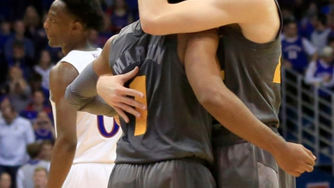 FILE - In this Sunday, Dec. 10, 2017, file photo Arizona State guards Kodi Justice, right, and Remy Martin (1) embrace in the final seconds of an NCAA college basketball game against Kansas in Lawrence, Kan. Arizona State plays Syracuse in the First Four at Dayton, Ohio on Wednesday, March 14, 2018. (AP Photo/Orlin Wagner, FIle)