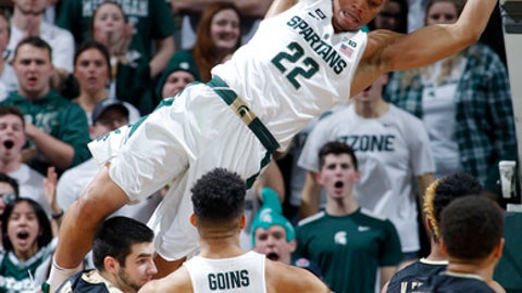 FILE - In this Feb. 10, 2018, file photo, Michigan State's Miles Bridges (22) dunks against Purdue's Dakota Mathias (31) and Vincent Edwards, right rear, as Michigan State's Kenny Goins (25) and Purdue's P.J. Thompson (11) watch during the first half of an NCAA college basketball game, in East Lansing, Mich. Miles Bridges turned down his first chance to make millions in the NBA to chase a priceless championship, choosing to stay at Michigan State for his sophomore season. (AP Photo/Al Goldis)