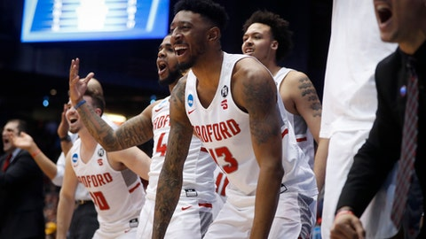 Radford's Leroy Butts IV (13) and the Radford bench react during the second half of a First Four game of the NCAA men's college basketball tournament against LIU Brooklyn, Tuesday, March 13, 2018, in Dayton, Ohio. Radford won 71-61. (AP Photo/John Minchillo)
