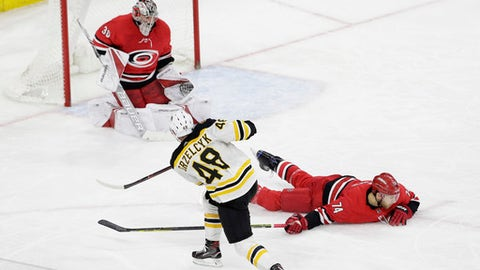 Boston Bruins' Matt Grzelcyk (48) scores against Carolina Hurricanes goalie Cam Ward (30) as Hurricanes' Jaccob Slavin (74) dives to block during the third period of an NHL hockey game in Raleigh, N.C., Tuesday, March 13, 2018. Boston won 6-4. (AP Photo/Gerry Broome)