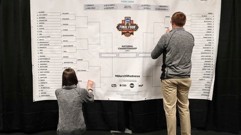 FILE - In this March 23, 2017, file photo, staff members for the NCAA place the names of the teams in the Sweet 16 on a bracket in the media work room before the start of practices, at the East Regional of the NCAA college basketball tournament in New York. You think brackets are just for basketball and that they only get filled out at this time of year, in the days leading up to the start of the NCAA Tournament? If so, think again. Of course, the NCAAs and the billions of dollars spent in bracket pools move the needle more than anything else. But these days, there are brackets for just about everything _ best presidents, best movies, best Aerosmith songs, and so much more. (AP Photo/Julie Jacobson, File)