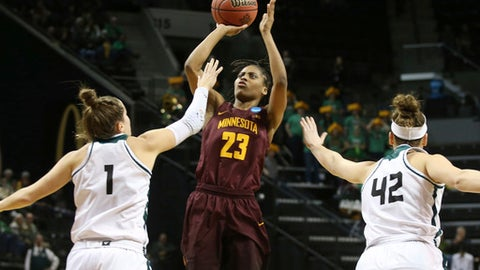 Minnesota's Kenisha Bell, center, shoots between Green Bay's Jen Wellnitz, left, and Mackenzie Wolf during the second half of a first-round game in the NCAA women's college basketball tournament in Eugene, Ore., Friday, March 16, 2018. (AP Photo/Chris Pietsch)