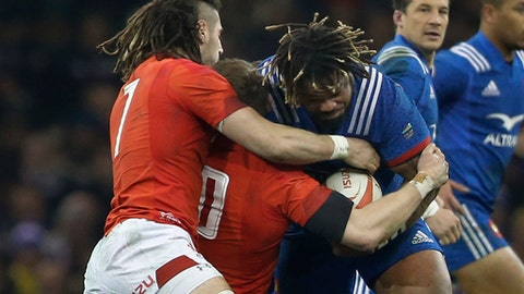 France's Mathieu Bastareaud , centre, is grabbed by Wales' Josh Navidi, left, and Wales' Dan Biggar during the Six Nations rugby union match between Wales and France at the Millennium stadium in Cardiff, Wales, Saturday, March 17, 2018. (AP Photo/Alastair Grant)