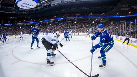 Vancouver Canucks' Daniel Sedin, right, of Sweden, passes the puck past San Jose Sharks' Evander Kane during the third period of an NHL hockey game Saturday, March 17, 2018, in Vancouver, British Columbia. (Darryl Dyck/The Canadian Press via AP)