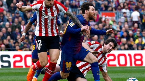 FC Barcelona's Lionel Messi, center, duels for the ball against Athletic Bilbao's Unai Nunez, left, during the Spanish La Liga soccer match between FC Barcelona and Athletic Bilbao at the Camp Nou stadium in Barcelona, Spain, Sunday, March 18, 2018. (AP Photo/Manu Fernandez)