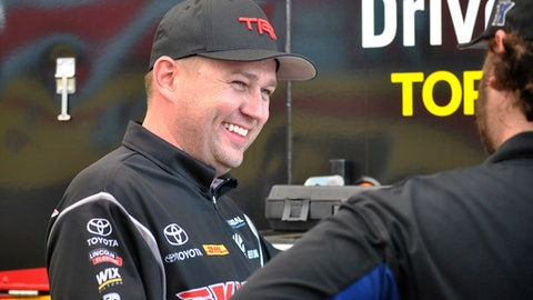 Richie Crampton smiles while talking with crew members before winning the Top Fuel final at the NHRA Gatornationals drag races Sunday, March 18, 2018, in Gainesville, Fla. (AP Photo/Mark Long)