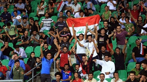 FILE - In this Oct. 5, 2017 file photo, Iraqi soccer fans display national flags as they cheer during a friendly soccer match between Kenya and Iraq, in Basra, Iraq. An Iraq-Qatar match, part of a friendly soccer tournament this week with Syria and Qatar, is to start Wednesday, March 21, 2018, in Basra. While friendly matches have been allowed for some time, last week FIFA lifted a three-decade ban on international competitions for the Iraqi cities of Basra, Karbala and Irbil, considered to be the safest in Iraq -- but not Baghdad, which still sees militant attacks. (AP Photo/Nabil al-Jourani, File)