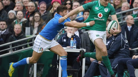 FILE - This is a Saturday, Feb. 10, 2018 file photo of Ireland's Jacob Stockdale, carries the ball as  Italy's Marcello Violi, left, attempts a tackle during the Six Nations rugby union match between Ireland and Italy at the Aviva stadium in Dublin, Ireland. Winger Jacob Stockdale has been chosen the best player of the Six Nations after scoring seven tries, the most in the championship in 93 years. Stockdale was a clear winner in the public vote, receiving 32 percent. (AP Photo/Peter Morrison/File)
