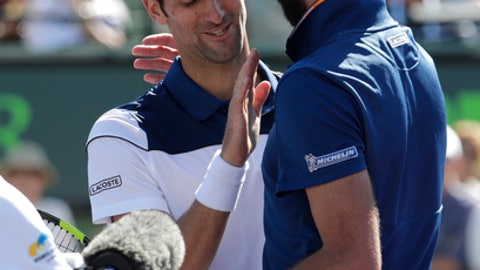 Novak Djokovic, of Serbia, left, meets Benoit Paire, of France, at the net after their match during the Miami Open tennis tournament, Friday, March 23, 2018, in Key Biscayne, Fla. Paire won 6-3, 6-4. (AP Photo/Lynne Sladky)