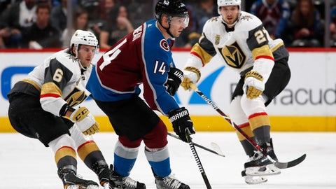 Colorado Avalanche left wing Blake Comeau, front, looks to pass the puck as Vegas Golden Knights defensemen Colin Miller, left, and Shea Theodore skate in during the second period of an NHL hockey game Saturday, March 24, 2018, in Denver. (AP Photo/David Zalubowski)