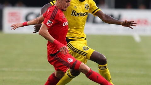 Toronto FC midfielder Marky Delgado, left, works against Columbus Crew midfielder Tony Tchani during the first half of an MLS soccer match in Columbus, Ohio, Wednesday, July 13, 2016. (AP Photo/Paul Vernon)