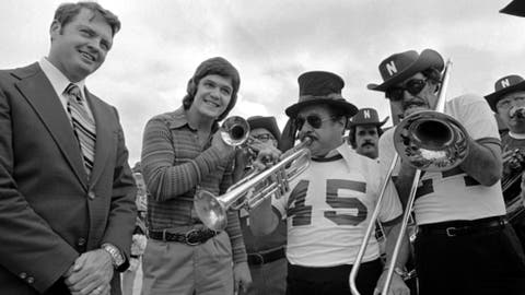 FILE - In this December 1974 file photo, Nebraska quarterback Dave Humm stands next to coach Tom Osborne, left, as they listen to a Dixieland jazz band greeting upon arrival in New Orleans for the Sugar Bowl college football game. Humm, a former star quarterback at Nebraska who had a long career as a backup in the NFL, has died. He was 65. The Raiders announced Humm's death on Wednesday, March 28, 2018, calling him a true Raider for his seven years with the team. (AP Photo, File)
