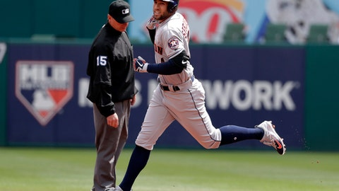Second base umpire Ed Hickox, left, watches as Houston Astros' George Springer, right, rounds second after hitting a solo home run off Texas Rangers' Cole Hamels on a lead at-bat in the first inning of a baseball game in Arlington, Texas, Thursday, March 29, 2018. (AP Photo/Tony Gutierrez)