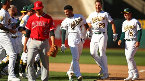 Oakland Athletics' Marcus Semien, center, celebrates with Matt Olson (28) and Jake Smolinski (5) after driving in the winning run in the the 11th inning of a baseball game against the Los Angeles Angels on Thursday, March 29, 2018, in Oakland, Calif. (AP Photo/Ben Margot)