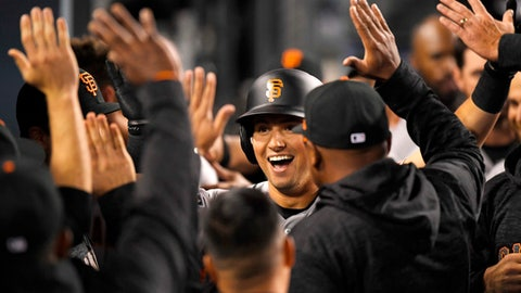 San Francisco Giants' Joe Panik is congratulated by teammates after hitting a solo home run during the ninth inning of a baseball game against the Los Angeles Dodgers Friday, March 30, 2018, in Los Angeles. (AP Photo/Mark J. Terrill)