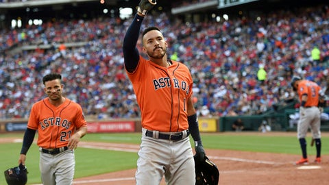 Houston Astros' Carlos Correa (1) acknowledges the crowd after hitting a home run which scored Jose Altuve, left, in the seventh inning of a baseball game against the Texas Rangers, Saturday, March 31, 2018, in Arlington, Texas. (AP Photo/Jeffrey McWhorter)
