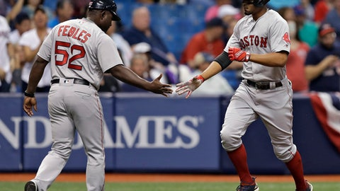 Boston Red Sox's Xander Bogaerts, right, shakes hands with third base coach Carlos Febles, left,  after Bogaerts' home run off Tampa Bay Rays' Andrew Kittredge during the second inning of a baseball game Saturday, March 31, 2018, in St. Petersburg, Fla. (AP Photo/Chris O'Meara)