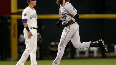 Colorado Rockies' Charlie Blackmon (19) rounds the bases after hitting a solo home run as Arizona Diamondbacks' Jake Lamb looks away during the sixth inning of a baseball game Saturday, March 31, 2018, in Phoenix. (AP Photo/Matt York)