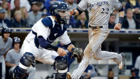 Milwaukee Brewers' Christian Yelich, right, scores on a single by Lorenzo Cain as the throw arrives late to San Diego Padres catcher Austin Hedges during the fourth inning of a baseball game in San Diego, Saturday, March 31, 2018. (AP Photo/Alex Gallardo)