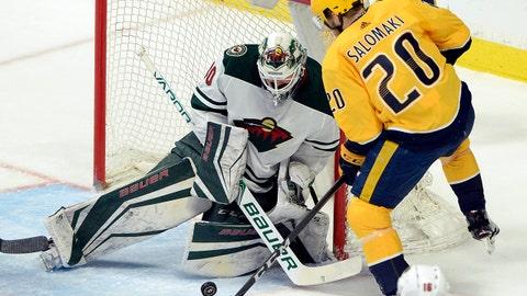 Minnesota Wild goaltender Devan Dubnyk (40) blocks a shot by Nashville Predators right wing Miikka Salomaki (20), of Finland, during the first period of an NHL hockey game Tuesday, March 27, 2018, in Nashville, Tenn. (AP Photo/Mark Zaleski)