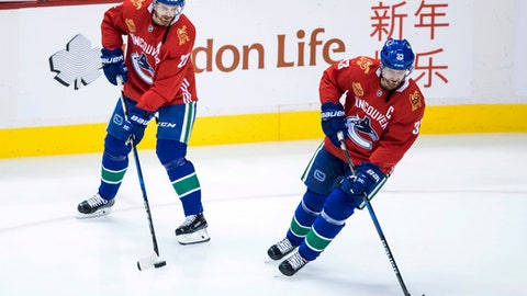 Vancouver Canucks' Daniel Sedin, left, and his twin brother, Henrik Sedin, wear jerseys to mark Chinese New Year while skating before the team's NHL hockey game against the Boston Bruins on Saturday, Feb. 17, 2018, in Vancouver, British Columbia. (Darryl Dyck/The Canadian Press via AP)