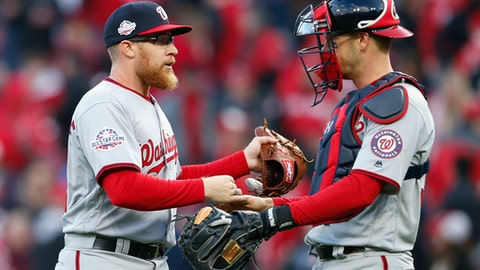 Washington Nationals relief pitcher Sean Doolittle, left, and catcher Matt Wieters, right, celebrates after closing the ninth inning of an opening day baseball game against the Cincinnati Reds, Friday, March 30, 2018, in Cincinnati. (AP Photo/Gary Landers)
