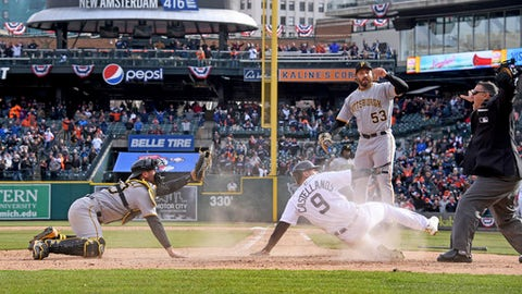 Detroit Tigers' Nick Castellanos (9) slides home as the ball arrives in the 10th inning Friday, March 30, 2018, during a baseball game against the Pittsburgh Pirates in Detroit. Castellanos was initially ruled safe, then out. (Dale G.Young/Detroit News via AP)