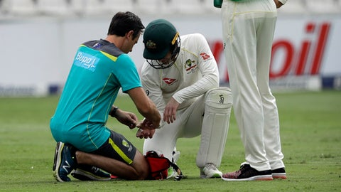 Australia's captain Tim Paine, right, receives treatment from a team medic after being hit by the ball on his right thumb on day three of the fourth cricket test match between South Africa and Australia at the Wanderers stadium in Johannesburg, South Africa, Saturday, March 31, 2018. (AP Photo/Themba Hadebe)