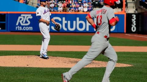 New York Mets pitcher Anthony Swarzak, left, watches St. Louis Cardinals' Matt Carpenter (13) runs the bases after hitting a home run during the eighth inning of a baseball game Saturday, March 31, 2018, in New York. (AP Photo/Frank Franklin II)