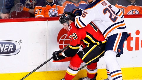 Edmonton Oilers' Darnell Nurse (25) vies for control of the puck with Calgary Flames' Micheal Ferland (79) during second period NHL action in Calgary on Saturday, March 31, 2018. (Larry MacDougal/The Canadian Press via AP)