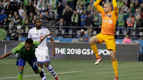 Montreal Impact goalkeeper Evan Bush, right, leaps to make a stop during the second half of an MLS soccer match against the Seattle Sounders, Saturday, March 31, 2018, in Seattle. The Impact won 1-0. (AP Photo/Ted S. Warren)