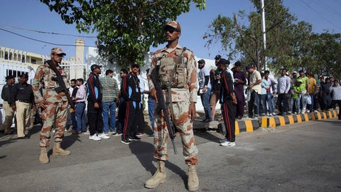 Pakistani paramilitary troops stand guard while cricket fans passing through a security checkpoint to enter in National Stadium for the 1st of three T20 match between Pakistan and West Indies cricket teams, in Karachi, Pakistan, Sunday April 1, 2018. (AP Photo/Fareed Khan)