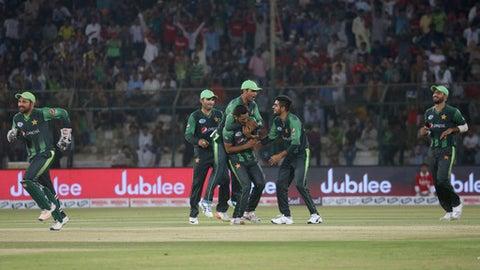 Pakistani pacer Hassan Ali, center, celebrates with teammates after taking wicket of West Indies batsman Denesh Ramdin during their 1st T20 cricket match at National stadium in Karachi, Pakistan, Sunday, April 1, 2018. (AP Photo/Fareed Khan)