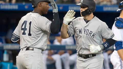 New York Yankees' Brandon Drury, right, celebrates his two-run home run against the Toronto Blue Jays with teammate Miguel Andujar during the third inning of their American League MLB baseball game in Toronto on Sunday April 1, 2018. (Fred Thornhill/The Canadian Press via AP)
