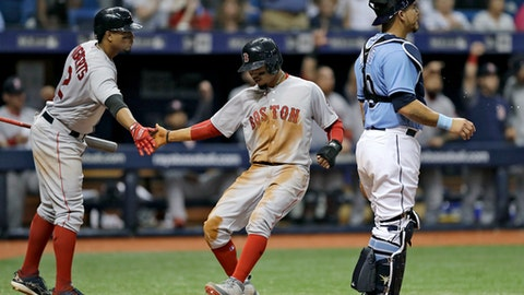 Boston Red Sox's Mookie Betts, center, shakes hands with on-deck batter Xander Bogaerts, left, after scoring past Tampa Bay Rays catcher Wilson Ramos on an RBI single by J.D. Martinez during the fifth inning of a baseball game Sunday, April 1, 2018, in St. Petersburg, Fla. (AP Photo/Chris O'Meara)