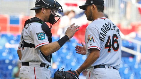 Miami Marlins catcher Chad Wallach, left, and relief pitcher Kyle Barraclough (46) congratulate each other after the Marlins defeated the Chicago Cubs 6-0 during a baseball game, Sunday, April 1, 2018, in Miami. (AP Photo/Wilfredo Lee)