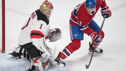 Montreal Canadiens' Brendan Gallagher moves in on New Jersey Devils goaltender Keith Kinkaid during the third period of an NHL hockey game in Montreal, Sunday, April 1, 2018. (Graham Hughes/The Canadian Press via AP)