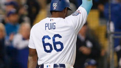 Los Angeles Dodgers' Yasiel Puig puts his hand in the air after scoring along with Yasmani Grandal on a double by Enrique Hernandez during the eighth inning of a baseball game against the San Francisco Giants on Sunday, April 1, 2018, in Los Angeles. The Dodgers won 9-0. (AP Photo/Danny Moloshok)