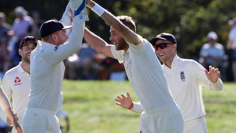 England's Stuart Broad, centre, is congratulated by teammate Jonny Bairstow, left, and Joe Root after taking the wicket of New Zealand's Kane Williamson during play on the final day of the second cricket test at Hagley Oval in Christchurch, New Zealand, Tuesday, April 3, 2018. (AP Photo/Mark Baker)
