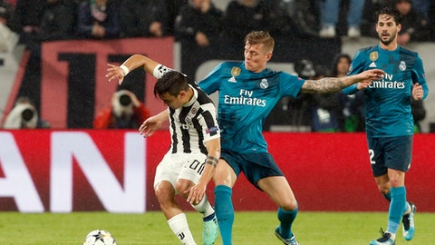 Juventus' Paulo Dybala, left, duels for the ball with Real Madrid's Toni Kroos during the Champions League first leg quarter final soccer match between Juventus and Real Madrid, at Juventus Stadium in Turin, Italy, Tuesday, April 3, 2018. (AP Photo/Antonio Calanni)