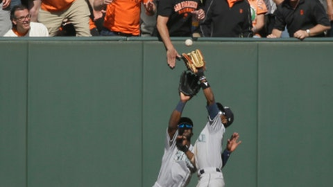 Seattle Mariners center fielder Dee Gordon, right, catches a fly ball hit by the San Francisco Giants' Nick Hundley in the seventh inning of a baseball game Tuesday, April 3, 2018, in San Francisco. Looking on is Mariners left fielder Guillermo Heredia. (AP Photo/Eric Risberg)